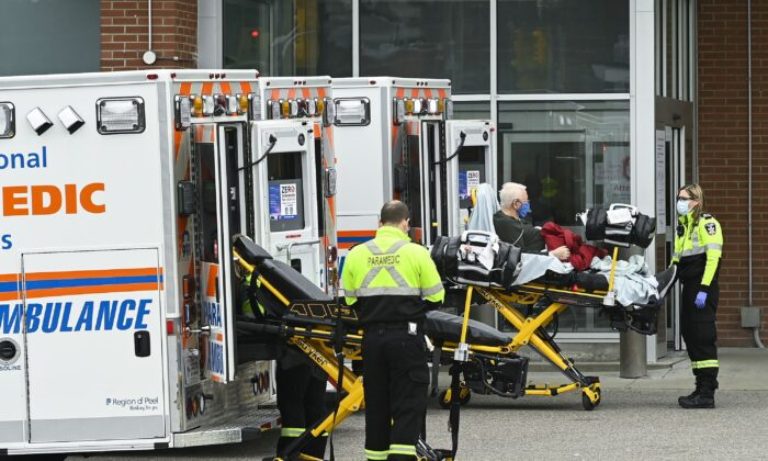 Paramedics transport a man to the emergency department of the Mississauga Hospital in Mississauga, Ont., on Nov. 19, 2020. (The Canadian Press/Nathan Denette)