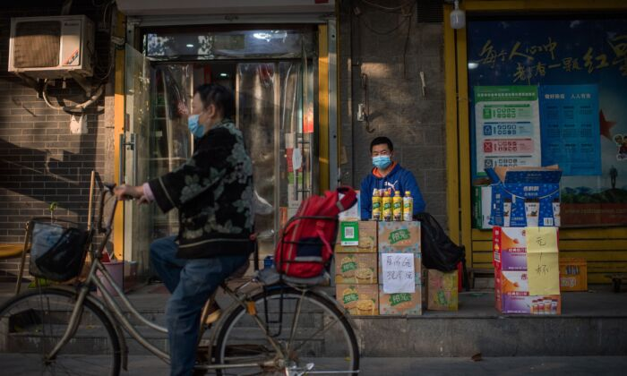 A vendor sells beverages outside a shop on a street in Beijing, China on Oct. 19, 2020. (NICOLAS ASFOURI/AFP via Getty Images)