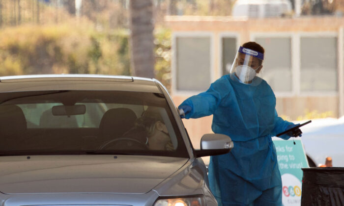 A COVID-19 testing site staff member conducts a temperature check at a drive-up testing site at the Orange County Fairgrounds in Costa Mesa, Calif., on Nov. 17, 2020. (Patrick T. Fallon/AFP via Getty Images)