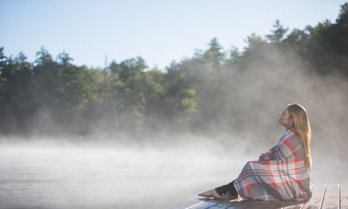 A guest enjoys a quiet moment on the lakeside dock on a misty morning. (Courtesy of Woodloch)