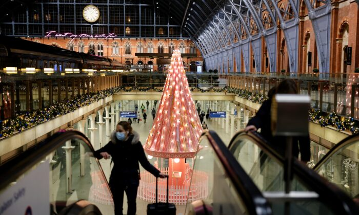 "A pedestrian wearing a face mask travels on an escalator near the ""Tree of Hope"" Christmas tree, installed inside St Pancras International train station in central London, on Nov. 23, 2020. (Tolga Akmen /AFP via Getty Images)"