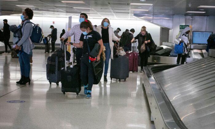 Travelers retrieve their luggage at Newark International Airport in Newark, N.J., on Nov. 21, 2020. (Kena Betancur/AFP via Getty Images)