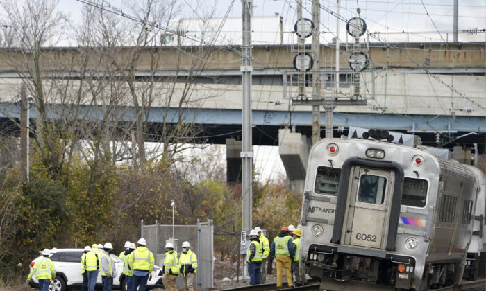 Emergency personnel talk near a derailed train in Perth Amboy, N.J., on Nov. 24, 2020. (Seth Wenig/AP Photo)