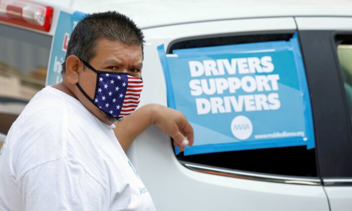 """Rideshare driver Jesus Jacobo Zepeda of Lancaster, California takes part in a rally as part of a statewide day of action to demand that ride-hailing companies Uber and Lyft follow California law and grant drivers """"basic employee rights,"""" in Los Angeles, Calif., on Aug. 20, 2020. (Mike Blake/Reuters)"""