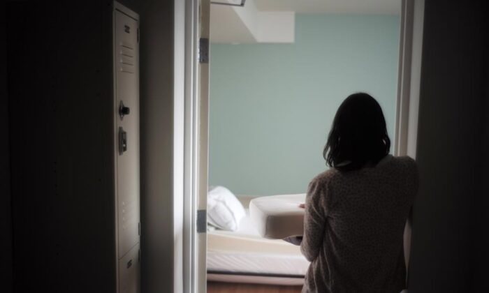 A staff member carries bedding in one of the suites at Toronto's Interval House, an emergency shelter for women in abusive situations, on Feb. 6, 2017. (THE CANADIAN PRESS/Chris Young)