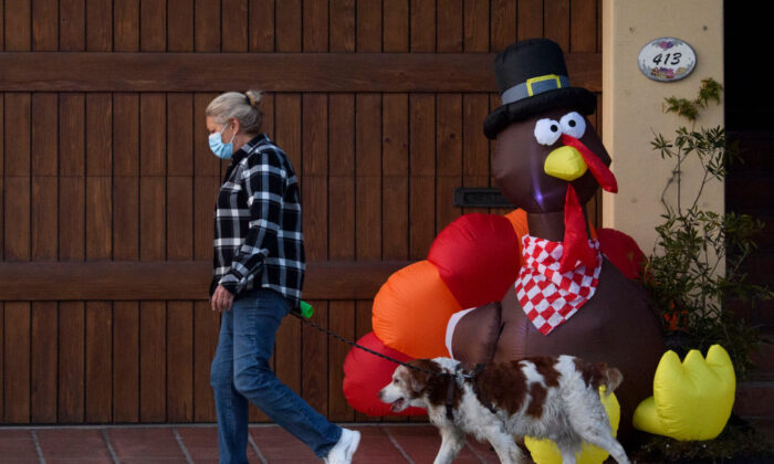A pedestrian wearing a mask walks her dog past an inflatable turkey ahead of the Thanksgiving holiday during increased COVID-19 restrictions in Manhattan Beach, Calif., on Nov. 21, 2020. (Patrick T. Fallon/AFP via Getty Images)