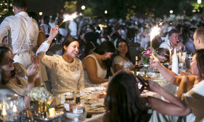 A global event called Diner en Blanc adopted the concept of al fresco dining, but with a white theme—from decor to guests' attire. Above, a Diner en Blanc at Nelson A. Rockefeller Park in Manhattan on Aug. 25, 2014. (Samira Bouaou/The Epoch Times)