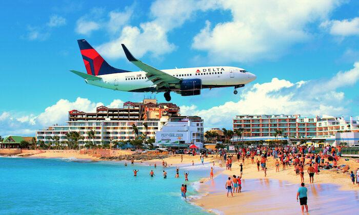An airplane flies over Maho Beach en route to Princess Juliana International Airport. (Gemma Fletcher/Shutterstock)