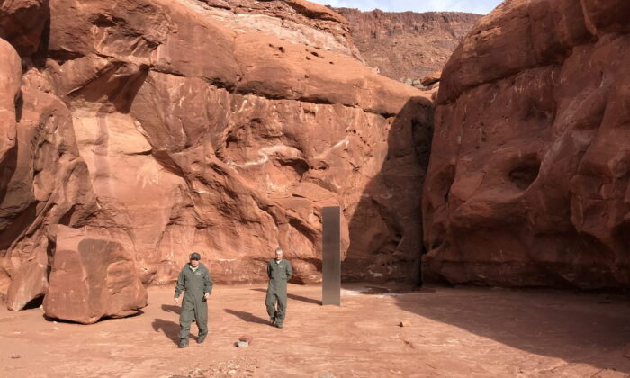 Utah Department of Public Safety Aero Bureau and Utah Division of Wildlife Resources crew members walk near a metal monolith they discovered in a remote area of Red Rock Country in Utah, U.S. on Nov. 18, 2020. (Utah Department of Public Safety via REUTERS)