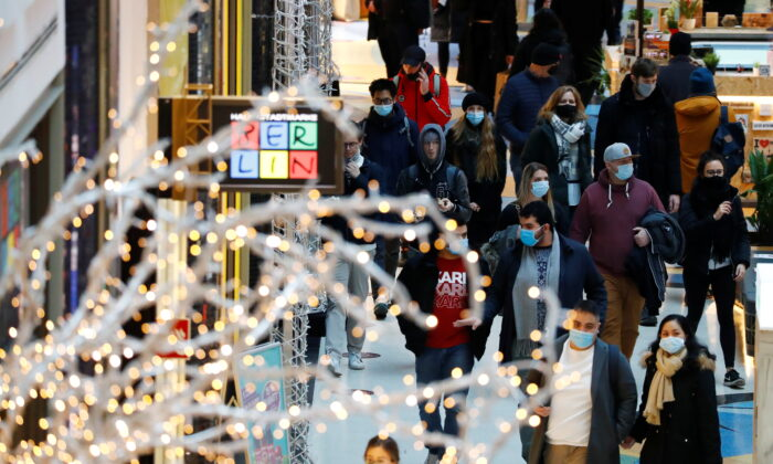 People wear protective face masks as they walk beside Christmas decoration at a shopping mall amid the coronavirus disease (COVID-19) outbreak in Berlin, Germany, on Nov. 21, 2020. (Fabrizio Bensch/Reuters)