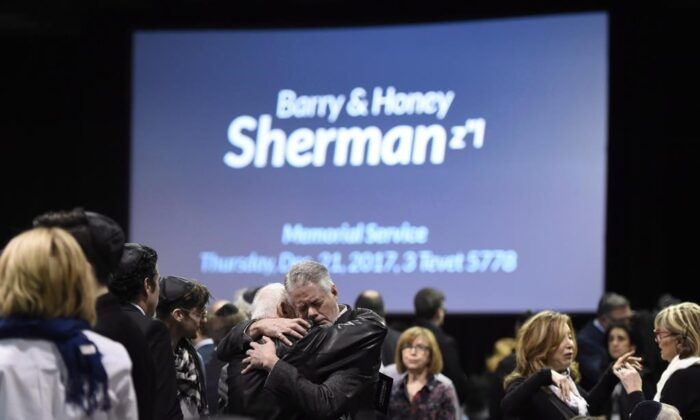 People embrace before the start a memorial service for Apotex billionaire couple Barry and Honey Sherman in Mississauga, Ontario on Dec. 21, 2017. (The Canadian Press/Nathan Denette)