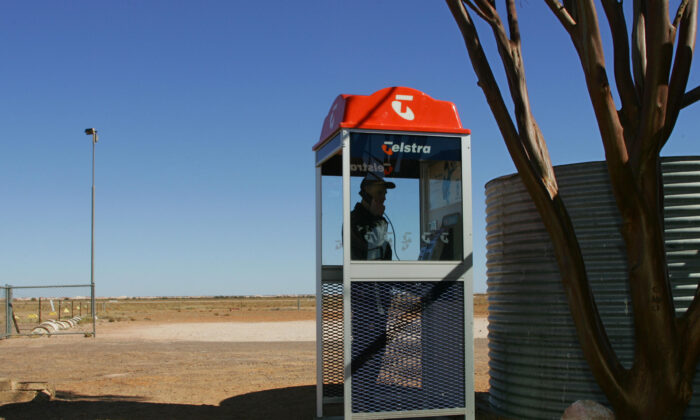 Tim Nagy makes a call from a Telstra public phone booth near the outback opal mining community of Coober Pedy, Australia, on July 5, 2005. (Torsten Blackwood/AFP via Getty Images)