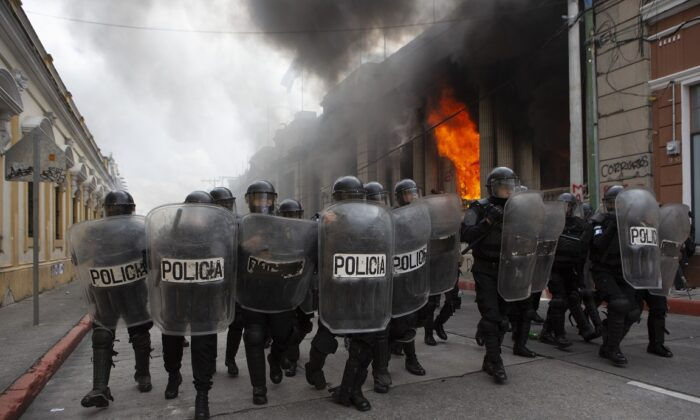 Riot police form a cordon as flames shoot out from the Congress building after protesters set a part of the building on fire, in Guatemala City on Nov. 21, 2020. (AP Photo/Oliver De Ros)