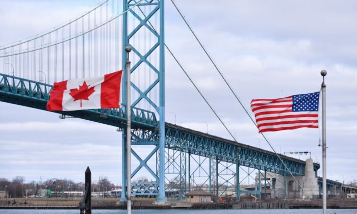 Canadian and American flags fly near the Ambassador Bridge at the Canada-USA border crossing in Windsor, Ont. on March 21, 2020. (The Canadian Press/Rob Gurdebeke)