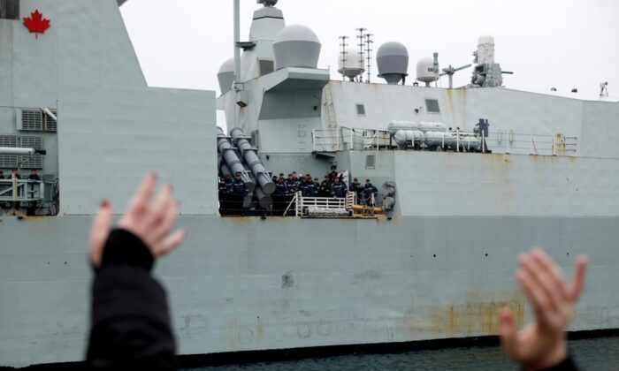 Family members and friends wait to welcome home the crew aboard the HMCS Ottawa following its four month deployment to the Asia-Pacific region as it returns to CFB Esquimalt in Victoria, B.C., on Dec. 18, 2019. (The Canadian Press/Chad Hipolito)