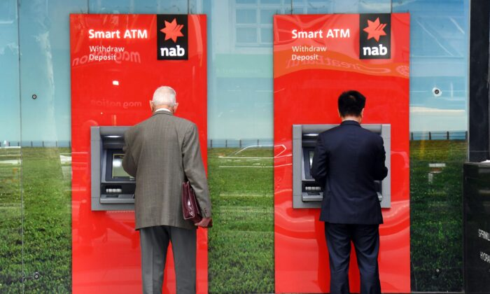 Two people use National Australia Bank (NAB) ATMs in Melbourne on May 2, 2019(William West/AFP via Getty Images)