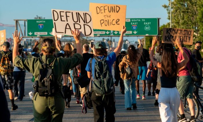 Protesters hold signs as they block the freeway during a demonstration calling for the removal of District Attorney Jackie Lacey and to defund the police, in Los Angeles, on July 1, 2020. (Valerie Macon/AFP via Getty Images)