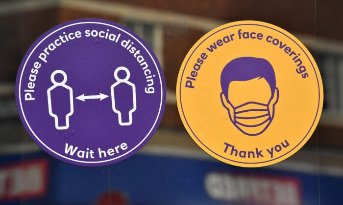 CCP virus information signs asking customer to wear face coverings and respect social distancing guidelines are pictured on the door of a bank branch in Sittingbourne in the Swale district of Kent, England, on Nov. 24, 2020. (Ben Stansall/AFP via Getty Images)