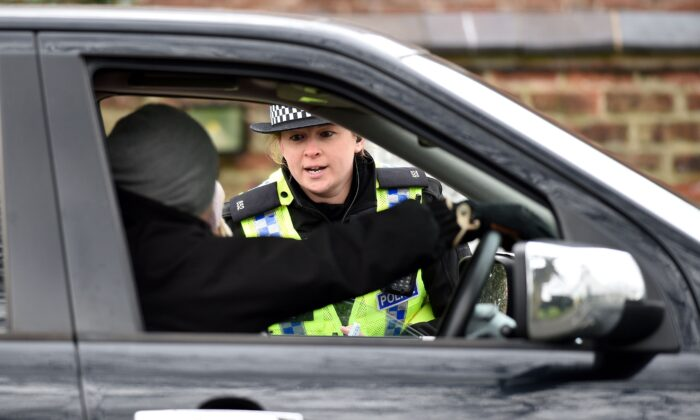 "During the first national lockdown, officers from North Yorkshire Police stop motorists in cars to check that their travel is ""essential"", in line with the British government's COVID-19 advice in York, northern England, on March 30, 2020. (Oli Scarff/AFP via Getty Images)"