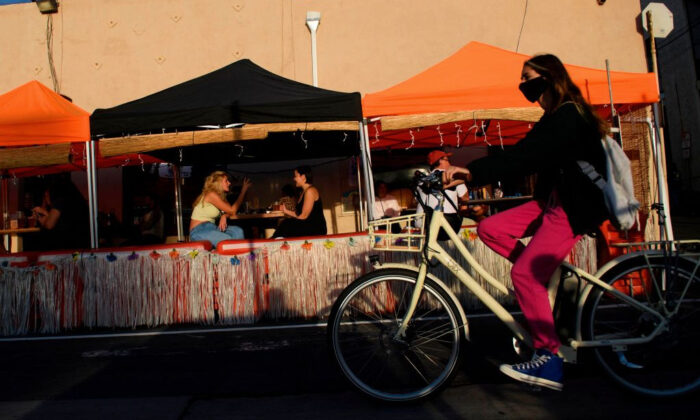 A cyclist wearing a face mask rides past outdoor diners in Manhattan Beach, Calif., on Nov. 21, 2020. (Patrick T. Fallon/AFP via Getty Images)