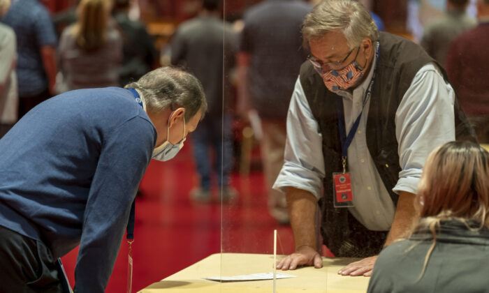 A representative for President Donald Trump (L) looks over a ballot during the presidential recount for Dane County in Madison, Wis., on Nov. 20, 2020. (Andy Manis/Getty Images)