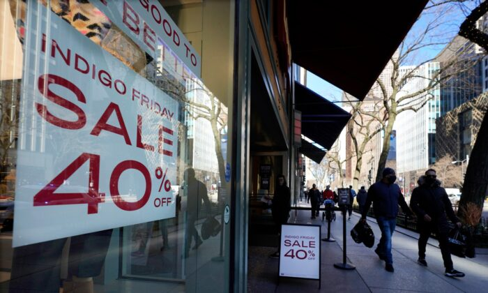 Shoppers pass an Indigo Friday 40% Off sign on Chicago's famed Magnificent Mile shopping district in Chicago, Ill., on Nov. 28, 2020. (Charles Rex Arbogast/AP Photo)