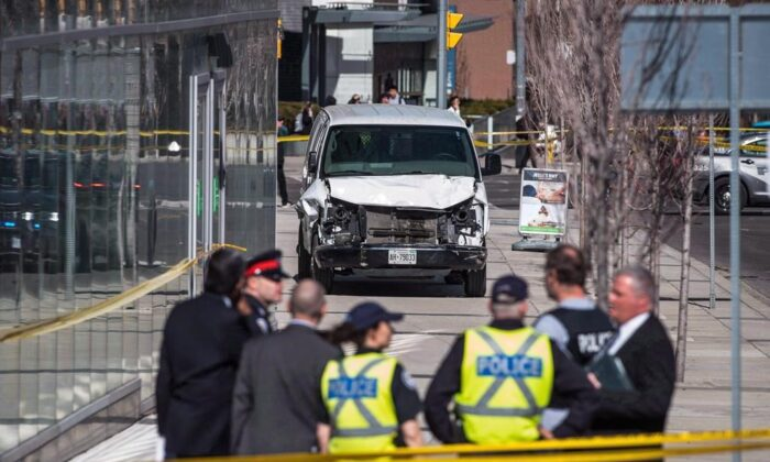 Police are seen near a damaged van in Toronto after the van mounted a sidewalk and crashed into a number of pedestrians on April 23, 2018. (The Canadian Press/Aaron Vincent Elkaim)
