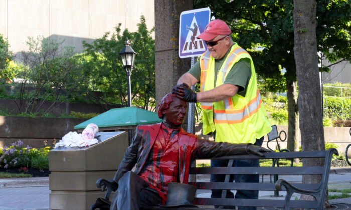 A worker cleans the Sir John A. Macdonald statue in Charlottetown on June 19, 2020, after it was defaced with red paint the previous night. (The Canadian Press/John Morris)