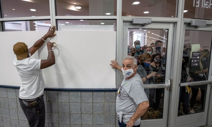 Poll workers board up windows so ballot challengers can't see into the ballot counting area at the TCF Center where ballots are being counted in downtown Detroit, Mich., on Nov. 4, 2020. (Seth Herald/AFP via Getty Images)