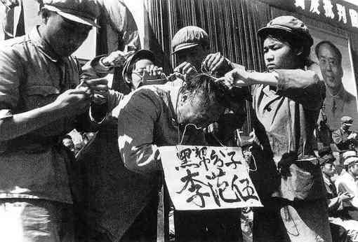 """Communist Party cadres hang a placard on the neck of a Chinese man during the Cultural Revolution in 1966. The words on the placard states the man's name and accuse him of being a member of the """"black class."""" (Public Domain)"""