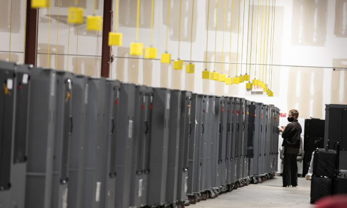 A Georgia Republican Party poll watcher looks over voting machine transporters being stored at the Fulton County Election Preparation Center in Atlanta, Ga., on Nov. 4, 2020. (Jessica McGowan/Getty Images)