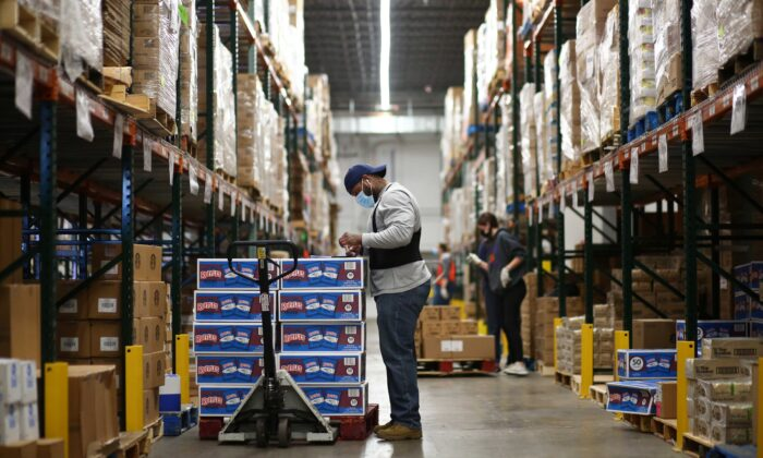 A staff member at Food Bank of the Rockies stocks boxes of food in their warehouse to be distributed to people in need ahead of Thanksgiving in Denver, Col., on Nov. 25, 2020. (Kevin Mohatt/Reuters)