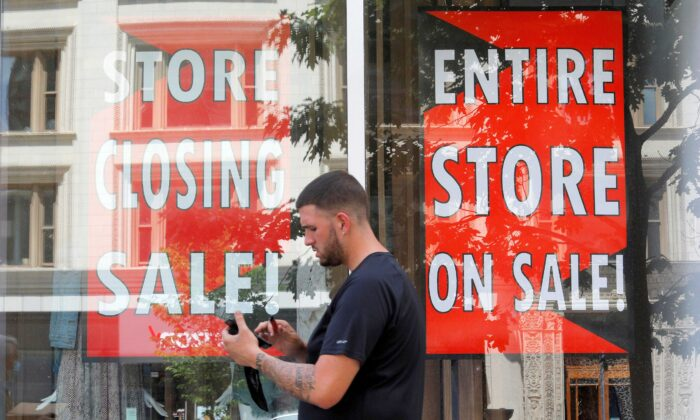 A man walks past signs in the windows of Lord & Taylor, advertising a store closing sale, in Boston, Mass., on Aug. 5, 2020. (Brian Snyder/Reuters)