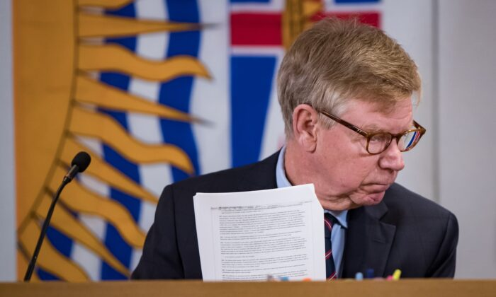 Commissioner Austin Cullen looks at documents before opening statements at the Cullen Commission of Inquiry into Money Laundering in British Columbia, in Vancouver, Canada, on Feb. 24, 2020. (Darryl Dyck/The Canadian Press)