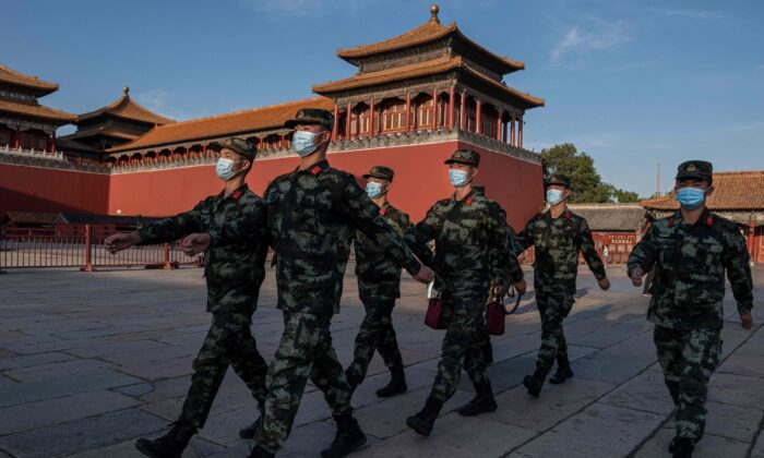 Paramilitary police officers wearing face masks march next to the entrance of the Forbidden City in Beijing, on Sept. 20, 2020. (Nicolas Asfouri/AFP via Getty Images)