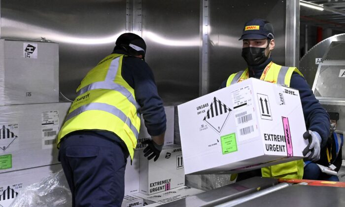 Workers at the DHL Express hub at Brussels Airport in Belgium, where COVID-19 vaccine manufacturer Pfizer is located, on Dec. 1, 2020. The airport has set up a task force to work on the logistics involved in the import and export of COVID-19 vaccines. (Dirk Waem/Belga Mag/AFP via Getty Images)