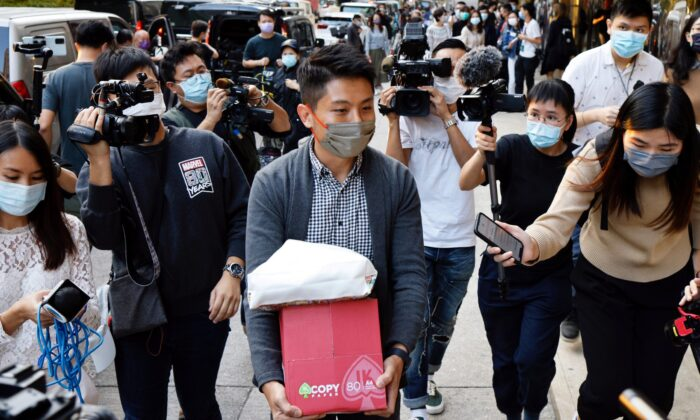 i-Cable TV news journalist leaves with a box after being laid off in Hong Kong on Dec.1, 2020. (Tyrone Siu/Reuters)