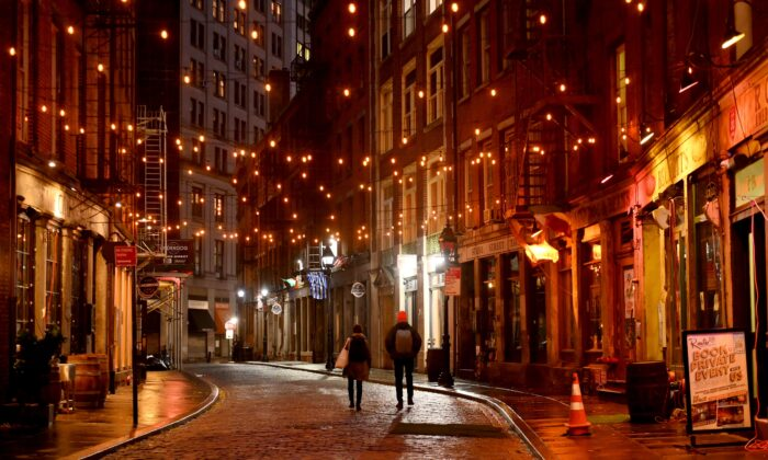 A couple walks along empty Stone Street in the financial district of New York City on Nov. 30, 2020. in New York City. (Angela Weiss/AFP via Getty Images)