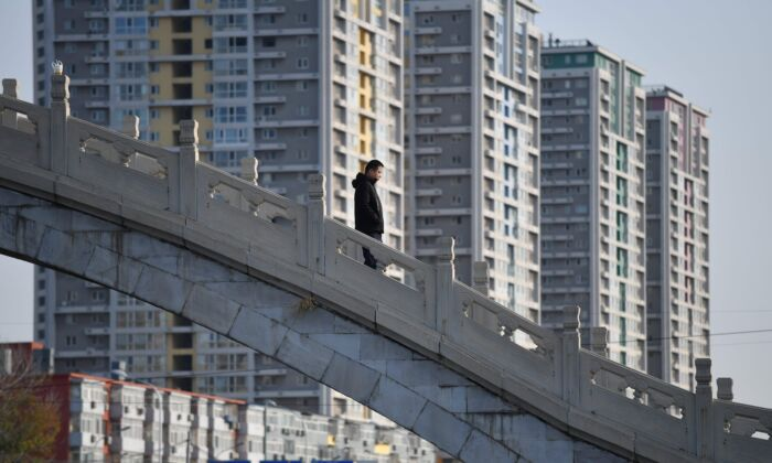 A man crosses a bridge near an apartment complex in Beijing, China, on Dec. 1, 2020. (Greg Baker/AFP via Getty Images)