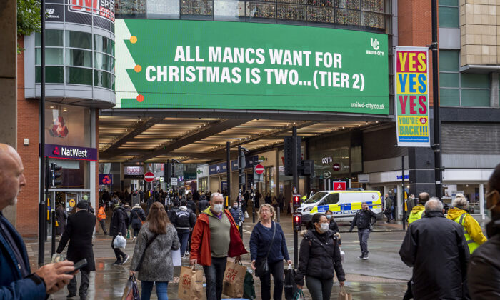 Shoppers walk past COVID-19 signage displayed on the Arndale in the city centre as Manchester, England, enters Tier 3 on Dec. 2, 2020 (Anthony Devlin/Getty Images)