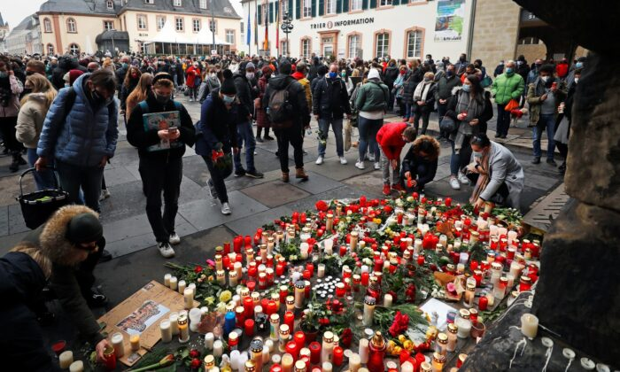 People pay their respects near the site where a car crashed into pedestrians in Trier, Germany, on Dec. 2, 2020. (Kai Pfaffenbach/Reuters)