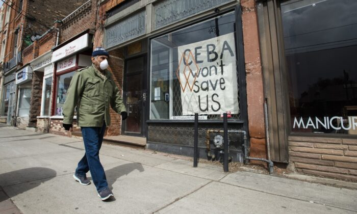 A closed store front boutique business called Francis Watson pleads for help displaying a sign in Toronto on April 16, 2020. (The Canadian Press/Nathan Denette)