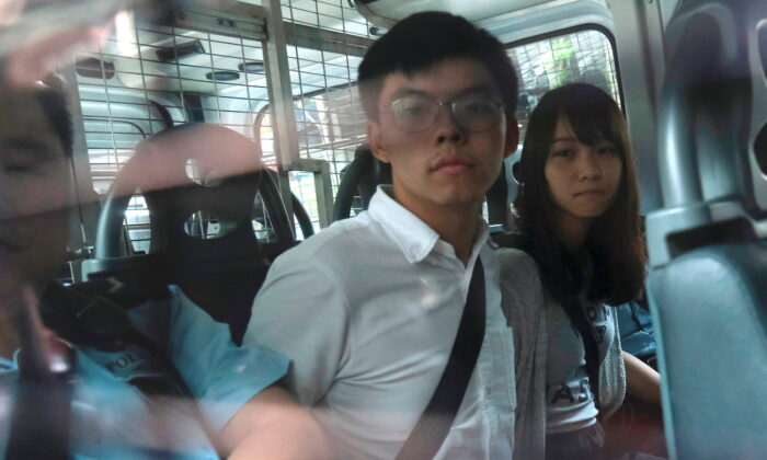 Pro-democracy activists Joshua Wong and Agnes Chow arrive at the Eastern Court by police van after being arrested in Hong Kong, on Aug. 30, 2019.(Tyrone Siu/Reuters)