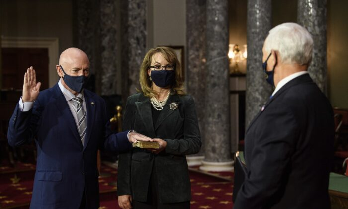 Sen. Mark Kelly, (D-Ariz.), with his wife, former Rep. Gabby Giffords (D-Ariz)., participates in a re-enactment of his swearing-in  by Vice President Mike Pence in the Old Senate Chamber on Capitol Hill in Washington on Dec. 2, 2020. (Nicholas Kamm/Pool via AP)