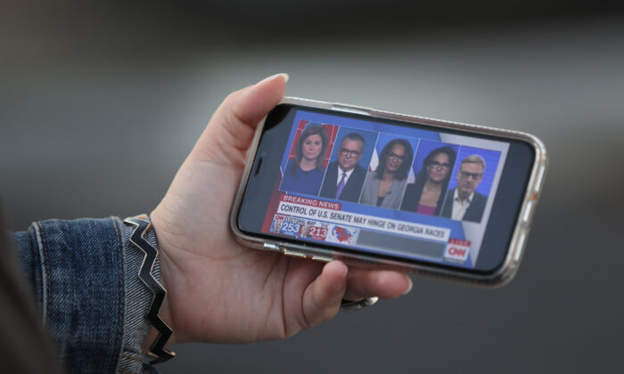 A person watches CNN on her phone in Wilmington, Delaware, on Nov. 6, 2020. (Joe Raedle/Getty Images)