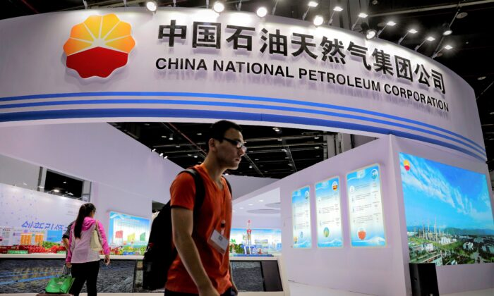 Visitors walk by the China National Petroleum Corporation (CNPC) booth during the China International Chemical Industry Fair in Shanghai, China, on Sept. 21, 2016. (AP Photo/Andy Wong)