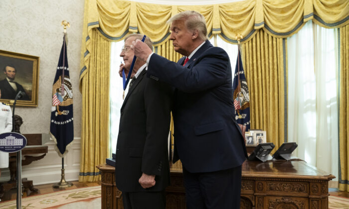 President Donald Trump presents the Presidential Medal of Freedom to former football coach Lou Holtz, in the Oval Office of the White House, in Washington, on Dec. 3, 2020. (AP Photo/Evan Vucci)