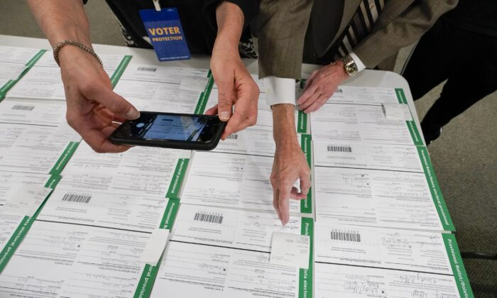 A canvas observer photographs Lehigh County provisional ballots as vote counting in the general election continues in Allentown, Pa., on Nov. 6, 2020. (Mary Altaffer/AP Photo)
