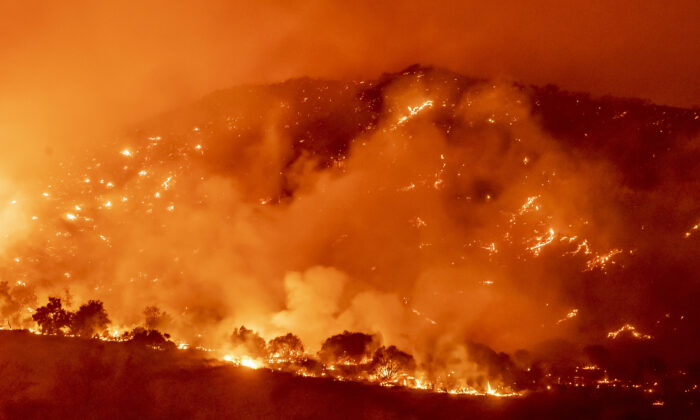 The Bond Fire, driven by high winds, burns the hillsides west of Santiago Canyon Road near Silverado Canyon, Calif., on Dec. 3, 2020. (Leonard Ortiz/The Orange County Register via AP)