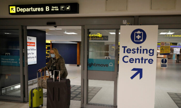 A passenger walks past a testing centre sign in the terminal building of Manchester Airport amid the outbreak of the coronavirus disease  in Manchester, UK, on Dec. 3, 2020. (Phil Noble/File Photo/Reuters)